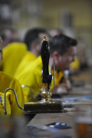 A single beer engine snaps into clear focus on a long bar of beer festival real ales.